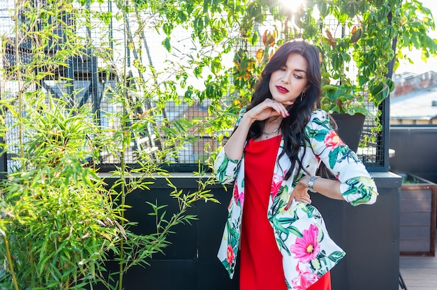 Belle brune jeune femme vêtue d'une robe rouge marchant dans la rue photo de mode