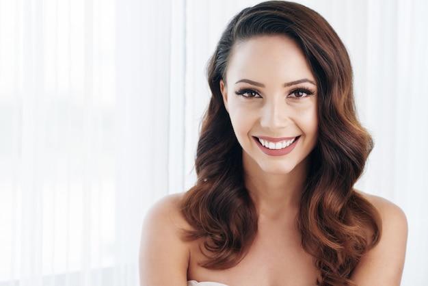 Belle brune avec maquillage, cheveux ondulés et épaules nues posant et souriant