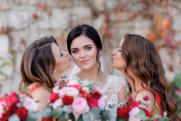 Belle brune mariée aux yeux bleus regarde droit et les demoiselles d'honneur s'embrassent presque sur les joues à l'extérieur avec un premier plan flou rose rouge