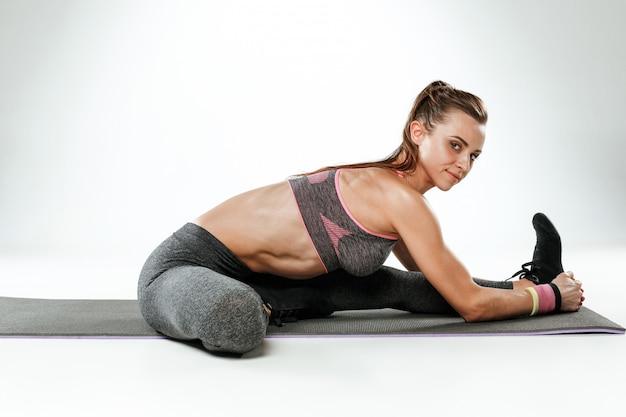 Belle brune mince faisant des exercices d'étirement dans une salle de sport