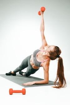 Belle brune mince faisant des exercices d'étirement