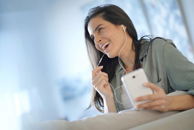 Belle brune parle au téléphone portable avec des écouteurs à la maison