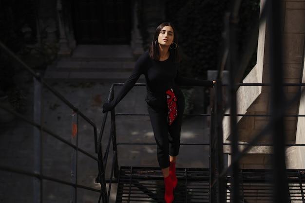 Belle brune posant sur un escalier noir