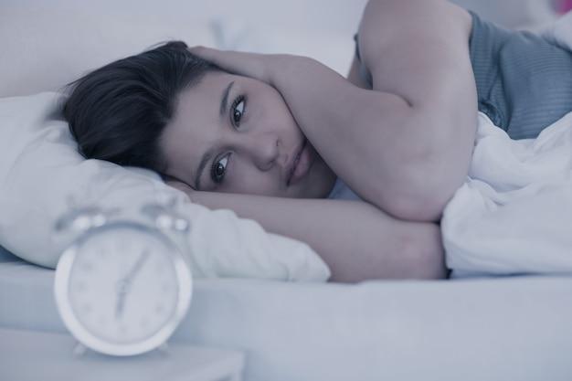 Belle brune regardant le réveil dans son lit