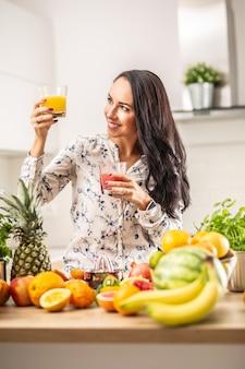 Belle brune regarde un verre de jus jaune dans une main, tenant du jus rouge dans l'autre.