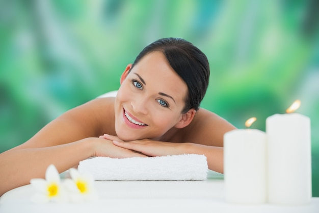 Belle brune relaxante sur la table de massage, souriant à la caméra