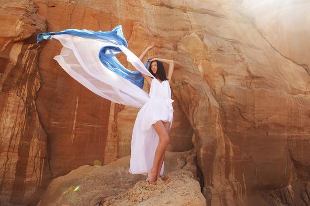 Belle brune en robe blanche avec tissu bleu dans le désert