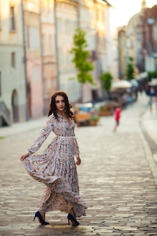 Belle brune sexy touriste fille marchant dans la rue animée de la ville aux cheveux longs, volant dans le vent.