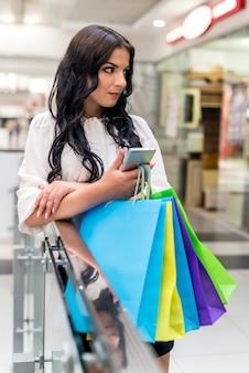 Belle brune sur le shopping avec téléphone dans un centre commercial