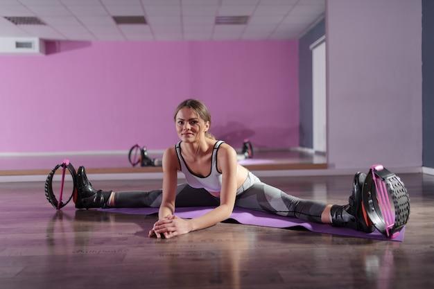 Belle brune souriante dans des vêtements de sport et des sauts de kangoo assis sur un tapis et des étirements.