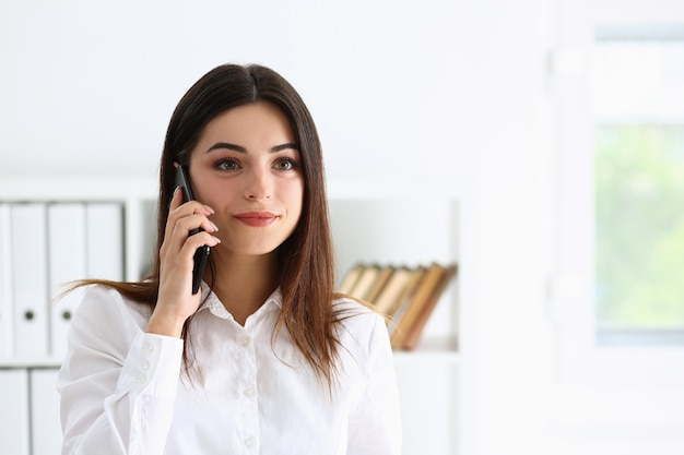 Belle brune souriante parler de femme d'affaires