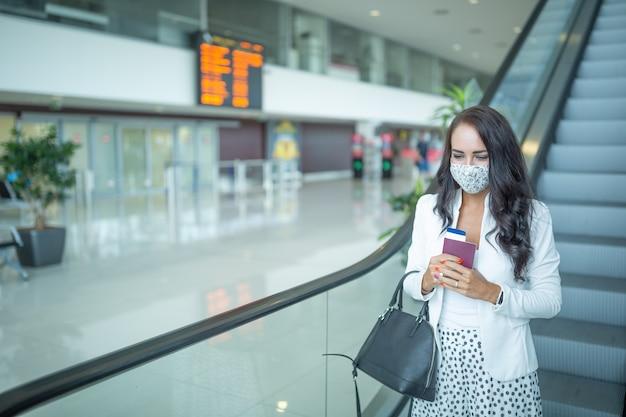 Belle brune en vêtements à la mode descend un escalator dans un aéroport avec passeport, carte d'embarquement et sac à main.