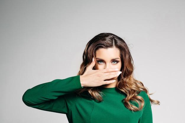 Belle brune vêtue d'une robe verte aux yeux bleus et aux cheveux bouclés, regarde dans l'appareil photo et couvre doucement sa bouche de sa main droite. isoler sur un fond gris