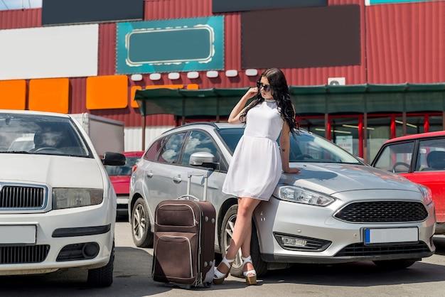 Belle brune voyageant avec valise sur voiture