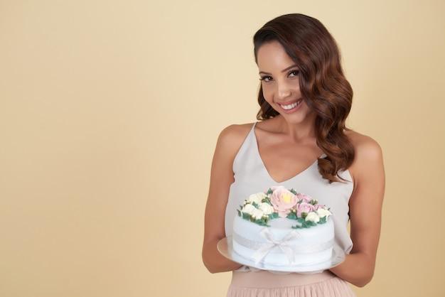 Belle brunette caucasienne qui pose en studio avec un beau gâteau