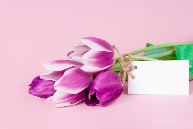 Belle carte de voeux avec des fleurs de tulipes sur fond rose