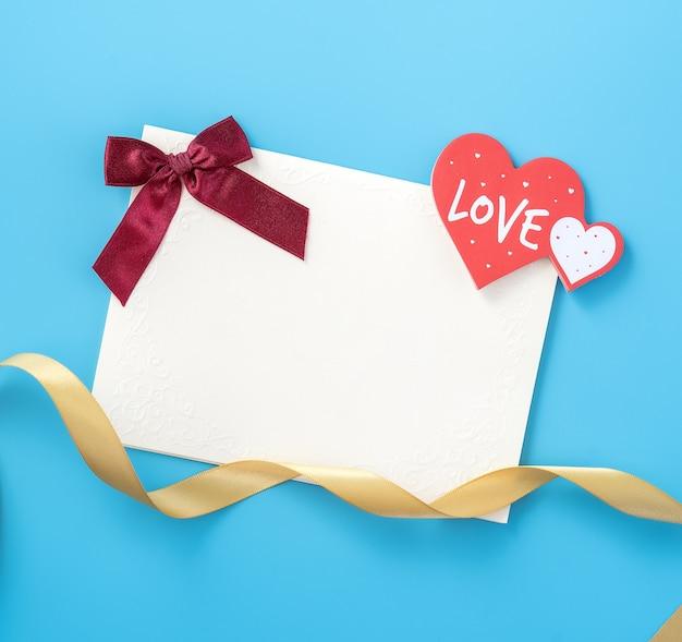 Belle carte de voeux avec ruban doré pour la saint valentin ou anniversaire flatlay