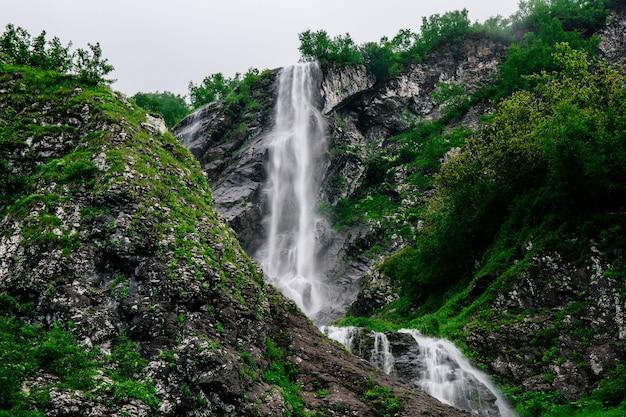 Belle cascade de montagne parmi les arbres fond naturel d'été