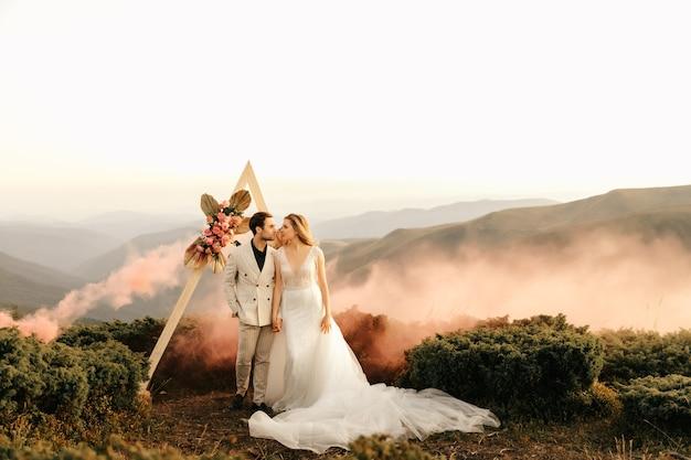 Belle cérémonie de mariage dans les montagnes, couple de mariés amoureux câlin.