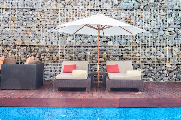Belle chaise de luxe avec parasol et piscine