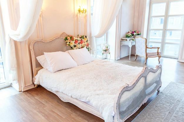 Belle chambre à coucher intérieure classique blanche lumineuse et propre de style baroque avec lit king-size, grande fenêtre, fauteuil et composition florale