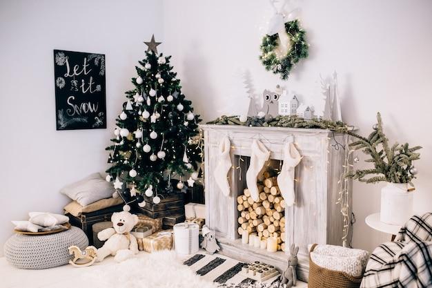 Belle chambre décorée avec arbre de noël avec des cadeaux en dessous