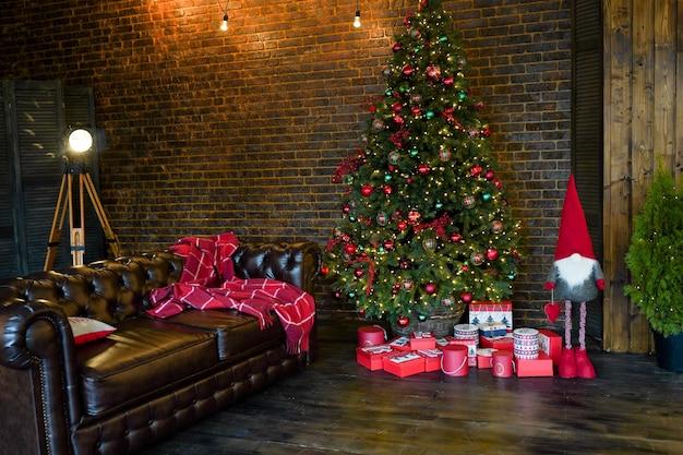 Belle chambre décorée de holdiay avec arbre de noël avec des cadeaux en dessous et un canapé sombre