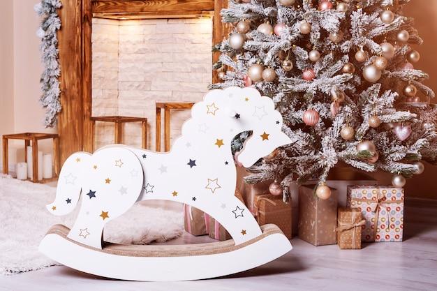 Belle chambre décorée de vacances avec arbre de noël, cheval en bois et cadeaux près de la cheminée.