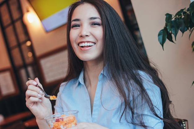 Belle charmante brune asiatique souriante a petit déjeuner avec pudding chia au café