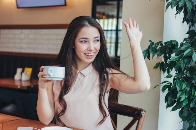 Belle charmante brune aux cheveux longs souriante jeune fille asiatique a petit-déjeuner avec café au café et saluant des amis