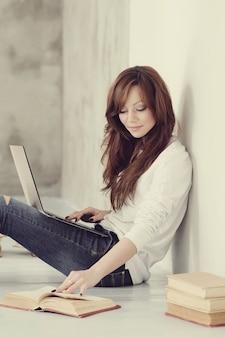 Belle et charmante femme adulte avec ordinateur portable et livres