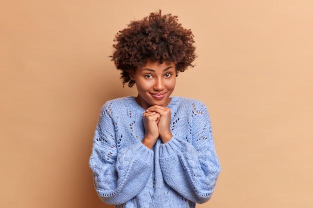 Belle charmante jeune femme aux cheveux bouclés garde les mains sous le menton a des sourires tendres et regarde directement à l'avant porte des poses de chandail décontracté contre le mur marron
