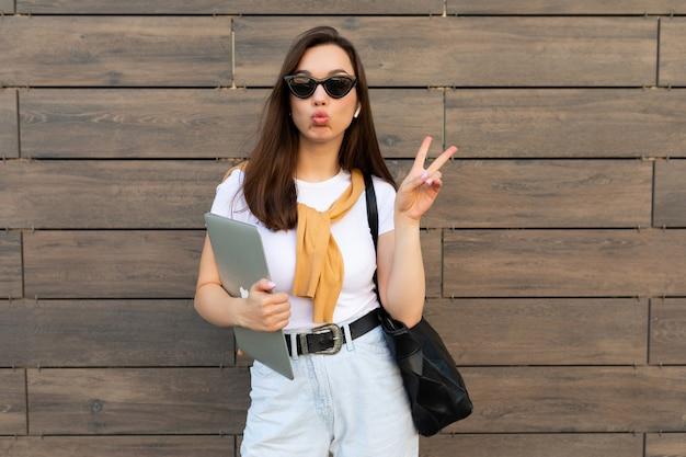 Belle charmante jeune femme brune regardant la caméra tenant un ordinateur portable et des lunettes de soleil