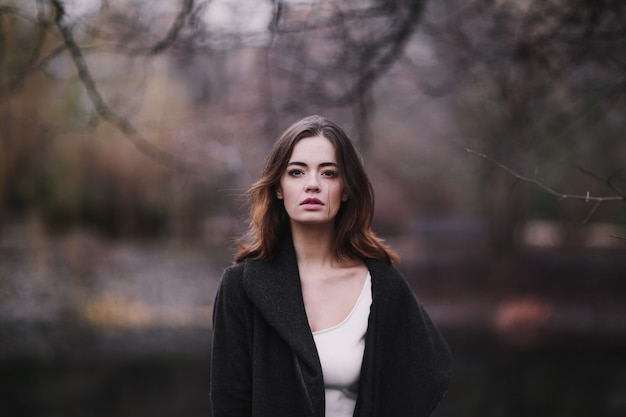 Belle charmante jeune femme vêtue d'une robe blanche et d'un manteau marchant dans le parc en automne.