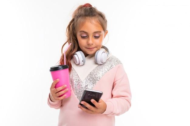 Belle charmante jeune fille dans un look d'hiver décontracté avec un casque blanc et une tasse de café à la main sur un mur blanc