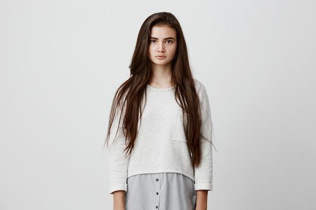 Belle charmante jolie jeune femme aux cheveux raides foncés posant sérieusement
