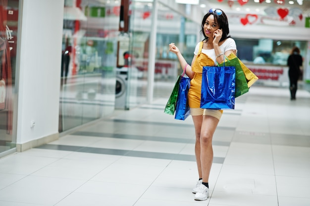 Belle cliente afro-américaine bien habillée avec des sacs à provisions colorés, parlant au téléphone au centre commercial.