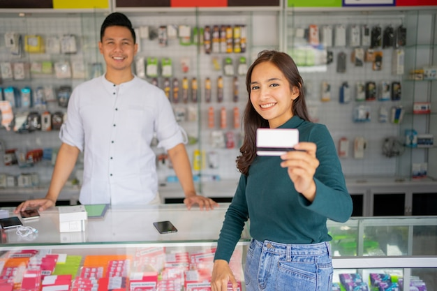 Une belle cliente montre une carte de crédit pour les payeurs non monétaires