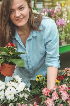 Belle cliente sentant des pots de fleurs en fleurs colorées dans le magasin de détail. jardinage en serre. jardin botanique, floriculture, concept de l'industrie horticole