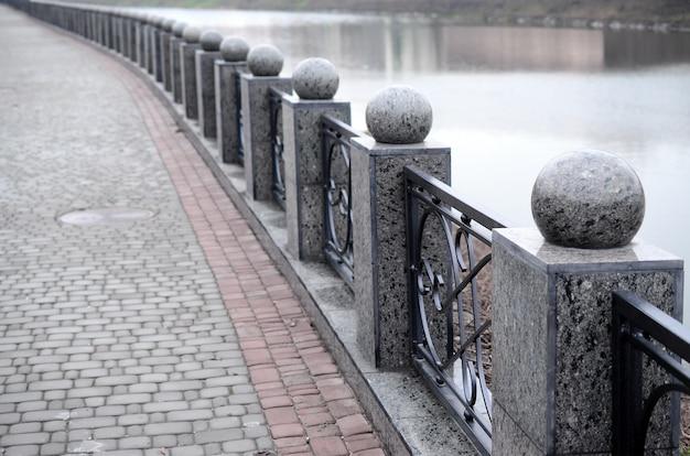 Une belle clôture en granit avec des sections en métal forgé et des boules décoratives comme décorations. la clôture est construite le long du talus de la rue