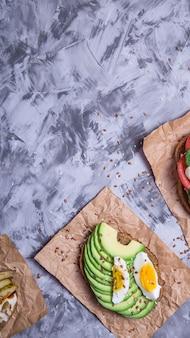 Belle collation saine - sandwichs avec du pain de seigle avec avocat et oeuf, mozzarella