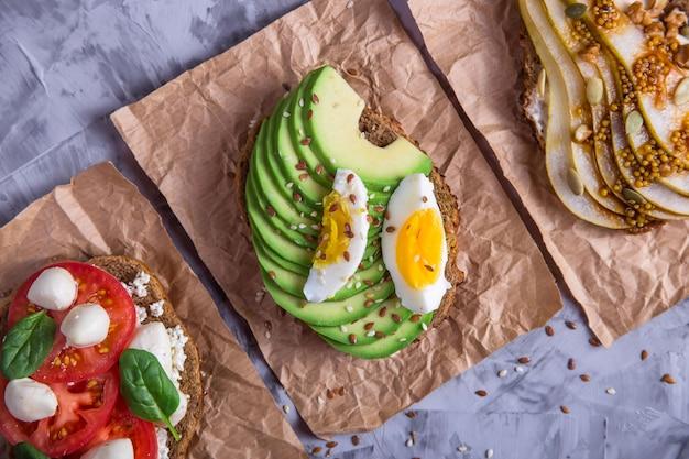 Belle collation santé - sandwiches avec du pain de seigle à l'avocat, mozzarella et tomate