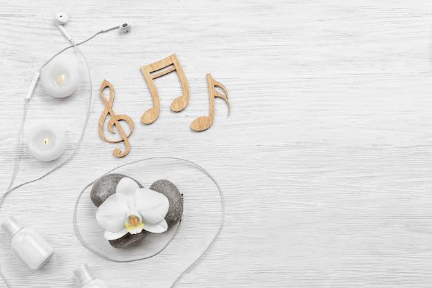 Belle composition d'accessoires de spa et de notes de musique sur une surface en bois blanche