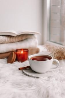 Belle composition d'automne avec bougie allumée et tasse de thé sur le rebord de la fenêtre