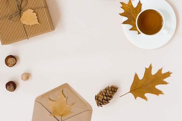 Belle composition d'automne avec une tasse de thé. feuilles d'automne, boîte cadeau kraft, une enveloppe et une couverture tricotée sur fond beige. le concept de la saison d'automne. espace de copie. automne plat poser