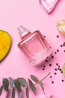 Belle composition avec flacon de parfum sur table rose