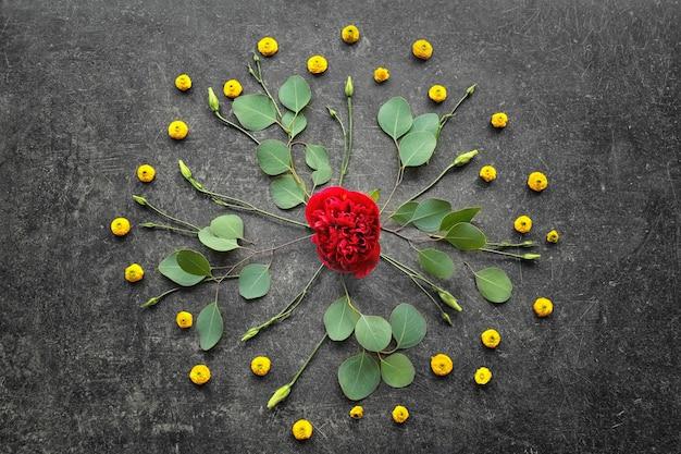Belle composition avec des fleurs et des feuilles sur une table grise