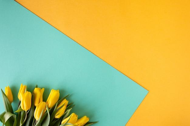 Belle composition florale. tulipes de fleurs jaunes, cadre vide pour le texte sur fond jaune. mariage. anniversaire de la saint-valentin. fête des mères. mise à plat, vue de dessus, espace copie