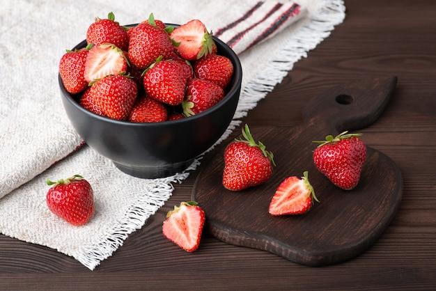 Belle composition de fraise mûre sur table sombre avec planche à découper et serviette en lin naturel