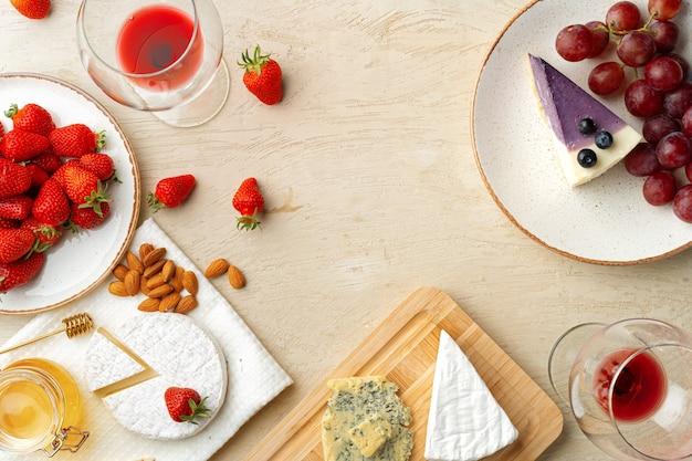 Belle composition avec gâteau au fromage aux fraises, raisins, fromage et myrtille